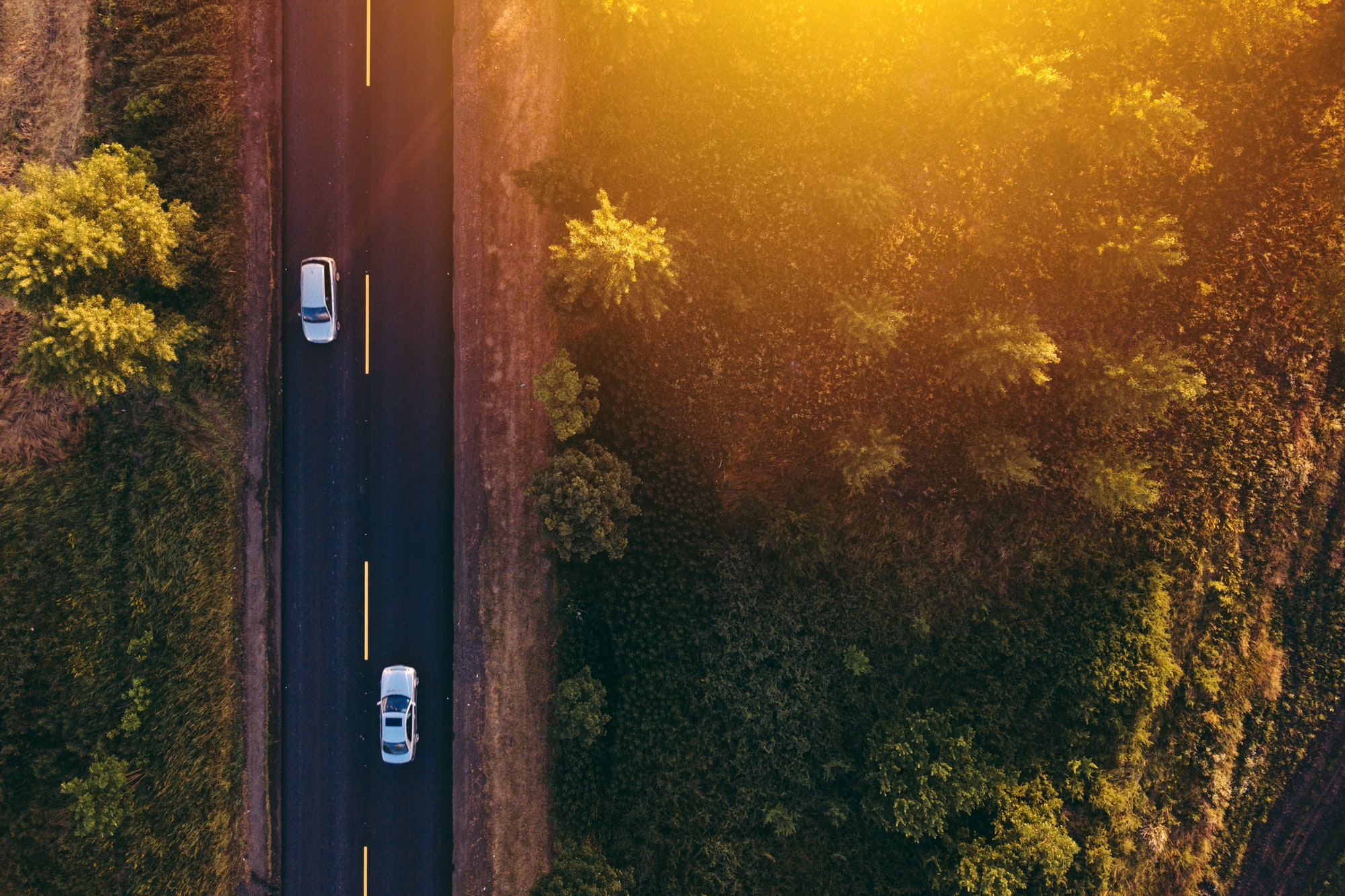 Aerial view of cars on the road in sunset